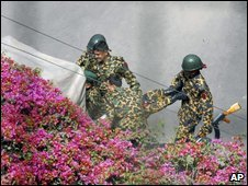 Bangladeshi border guards carry an injured colleague into the BDR headquarters