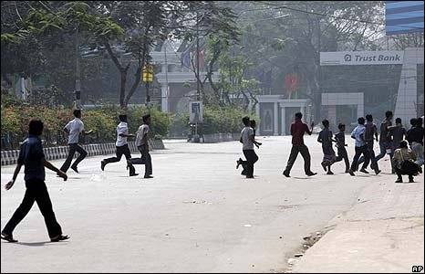 Civilians run for cover outside the headquarters of the Bangladesh Rifles in Dhaka on 25/2/09