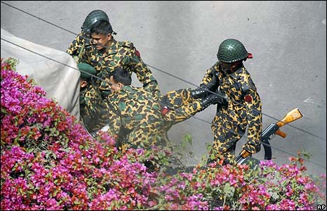 Border guards carry an injured colleague inside the Bangladesh Rifles HQ in Dhaka on 25/2/09