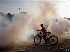 A boy stands on a bike as officials of the departmental health services fumigate during a campaign against Dengue fever in Santa Cruz, Bolivia