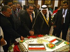 Hoshyar Zebari and Ali al-Momen cut cake