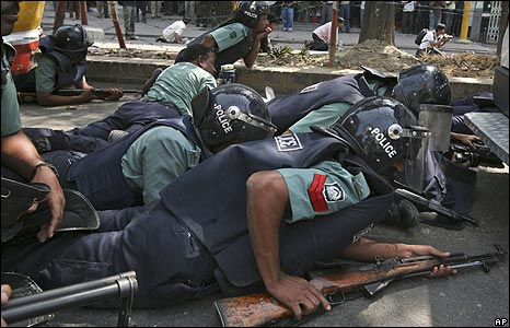 Policemen take cover as shots are fired outside the BDR headquarters in Dhaka, 26 Feb 2009