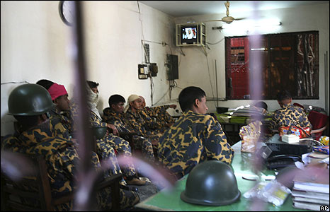 BDR guards listen to PM Hasina's televised speech inside the BDR headquarters in Dhaka 26 Feb 2009