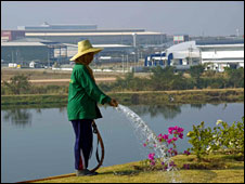 A man waters flowers opposite one of Thailand's big industrial estates along its eastern seaboard