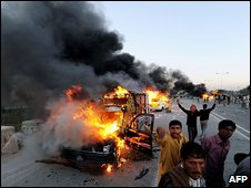 Supporters of former premier Nawaz Sharif shout slogans as they gather in front of burning vehicles during a protest in Islamabad on February 26, 2009