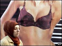 Una mujer pasa frente a una publicidad de ropa interior.