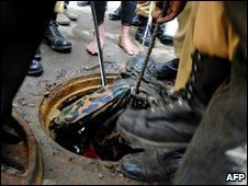 Searchers lift an officer's body from a manhole near the mutineers' barracks in Dhaka, 27 February