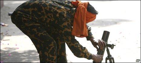 A Bangladesh border guard prepares to surrender a mortar