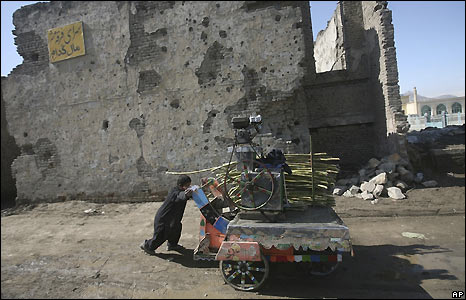 Boy in Kabul, Afghanistan, with sugar cane vendor's cart