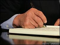 Hombre escribe en un cuaderno