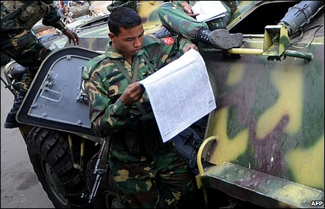 Soldier reading newspaper