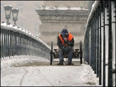 A snow-sweeper rests on his cart on the snow covered historical Chain Bridge of the River Danube in downtown Budapest