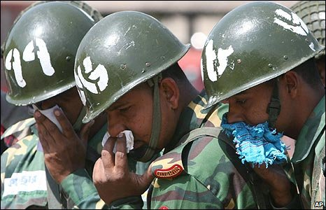 Bangladeshi soldiers cover their faces as a mass grave is investigated in Dhaka.