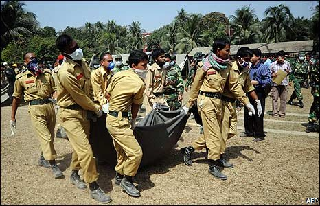 Bangladeshi firefighters carry the body of an army officer from a mass grave in Dhaka