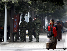 A Tibetan woman walks past Chinese security personnel in Chengdu, China, 28  February 2009