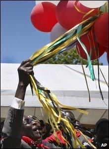 Robert Mugabe clutches birthday balloons