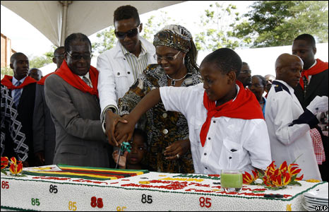 Mr Mugabe with his wife and two sons cutting the cake