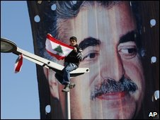 A Lebanese man waves a flag in front of a banner of former PM Rafik Hariri