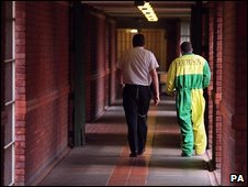 A prisoner being led down a corridor in a young offenders' insitute