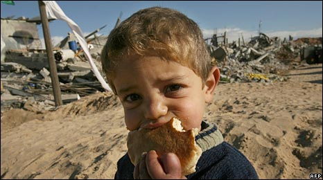 A Palestinian child eats bread near destroyed houses in Gaza. Photo: February 2009