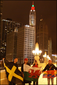 Members of the The Chicago Tafia Welsh Society wave their flags with the city's Wrigley building illuminated in red, white and green.