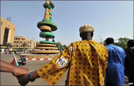 African film directors and cinema business representatives hold hands and circle a monument dedicated to the cinema in Ouagadougou
