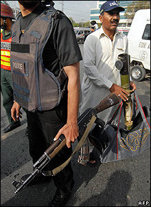 A Pakistani policeman (R) holds an empty rocket launcher