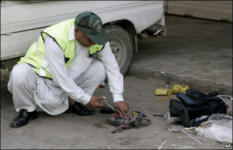 A bomb disposal expert disarms an explosive at the site of the attack on Sri Lankan cricket team.