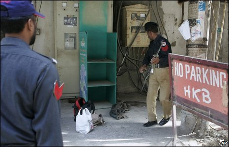 Pakistani police examine bags left at the scene of the attack on the Sri Lankan cricket team in Lahore.