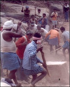 Villagers building a new road in Bihar shoving a big stone ahead of them
