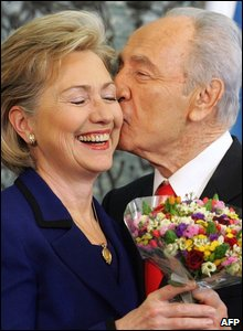 Israeli President Shimon Peres kisses US Secretary of State Hillary Clinton on her cheek as he gives her a bouquet of flowers