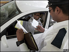 An Iraqi traffic police officer inspects a driver's vehicle registration papers at a checkpoint in central Baghdad  July 2008