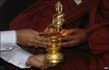 Sri Lanka's President Mahinda Rajapakse receives a golden buddha statute from monks in Kathmandu