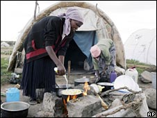Women prepare food outside their tent in an internally displaced persons camp in the Kenyan town of Naivasha, Nairobi,Kenya. Monday. Dec. 15 2008.