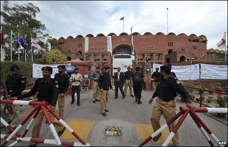 Pakistani policemen stand guard as a bus carrying security personnel enters The Gaddafi Stadium