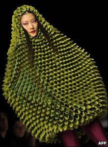 A model wears a green hooded armless garment by Agatha Ruiz De La Prada at fashion week in Milan