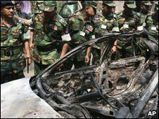 An army investigation team inspects a burned car at the BDR headquarters
