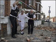 An elderly woman led through rubble in 2007
