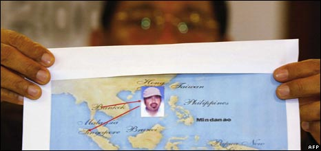 An Indonesian Police Officer holds a picture of Hambali, 07/03