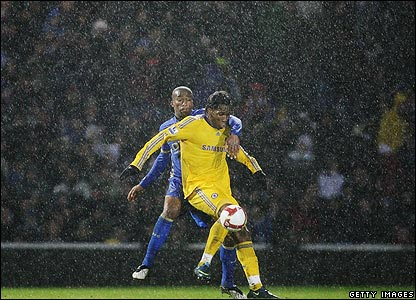 Portsmouth's Sylvain Distin pays close attention to the threat of Didier Drogba