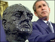George W Bush stands next to a bust of Winston Churchill given to the White House by the British government in 2001