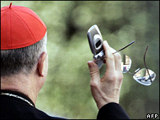 Italian Cardinal Tarcisio Bertone holds his mobile phone (2005)
