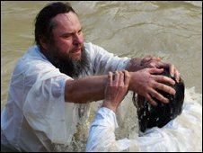 A Russian-Orthodox priest (L) baptises a Christian pilgrim