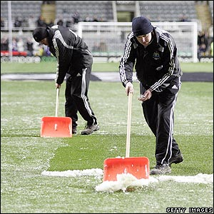 Newcastle groundstaff clear the pitch after wintry showers strike St James' Park