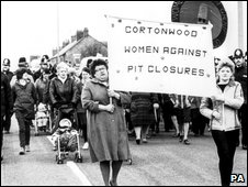 Women walking past Cortonwood Pit with banners flying as the pit strike draws to a close, 1985
