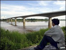 Lao man looks at bridge over Mekong July 03