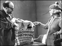 Man and woman looking at knitted jumper