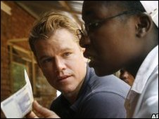US actor Matt Damon speaks with a Catholic nun from Zimbabwe who shows him a 10bn Zim dollars banknote at a church in the South African border town of Musina