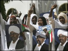Sudanese women hold pictures of Sudanese President Omar al-Bashir during a speech delivered by al-Bashir at the entrance of the presidential palace in Khartoum, Sudan Thursday, March 5, 2009