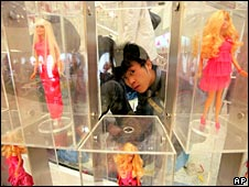 A worker cleans glass cases holding the different Barbie models on 5 March 2009